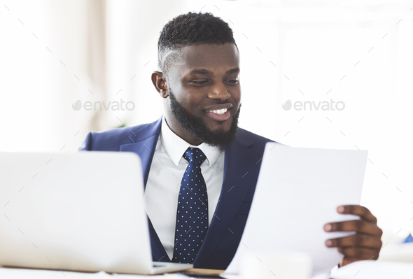 Smiling african american businessman checking reports in modern office - Stock Photo - Images