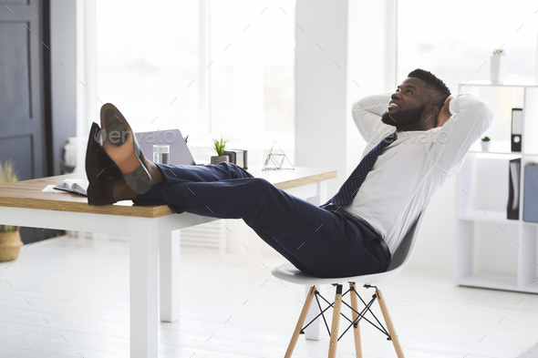 Joyful young manager relaxing on chair in white modern office - Stock Photo - Images