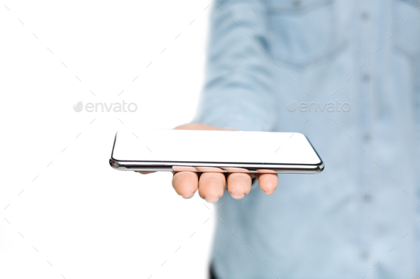 Woman holding modern smartphone with blank screen on open palm - Stock Photo - Images