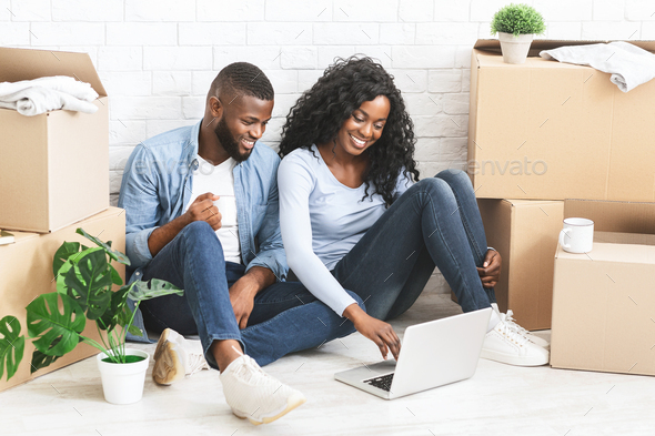Cheerful couple sitting on floor at new apartment, using laptop - Stock Photo - Images