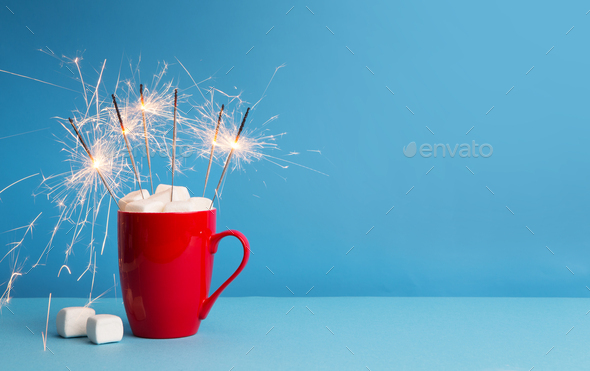 Sparklers in red cup with marshmallow and hot cocoa on blue - Stock Photo - Images
