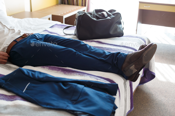 Man legs in formal trousers on hotel bed - Stock Photo - Images
