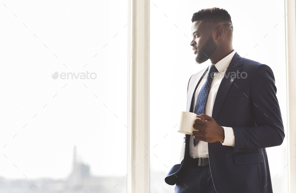 Young successful businessman drinking coffee in office - Stock Photo - Images