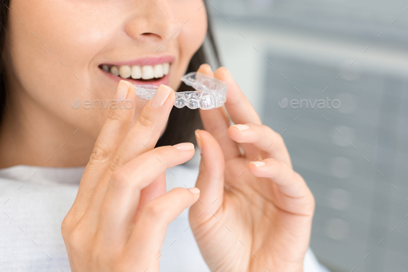 Girl holding invisible braces, moder teeth trainer - Stock Photo - Images