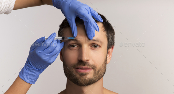 Mature Man Receiving Cosmetic Injection Standing Over White Background, Panorama - Stock Photo - Images