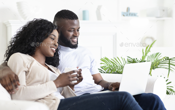 Cheerful black couple sitting on couch looking at laptop screen - Stock Photo - Images