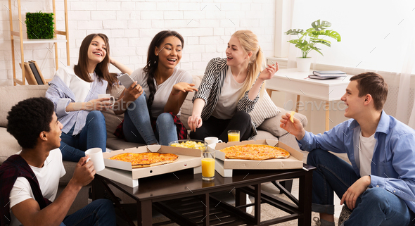 Home party. Teenagers eating pizza and chatting - Stock Photo - Images