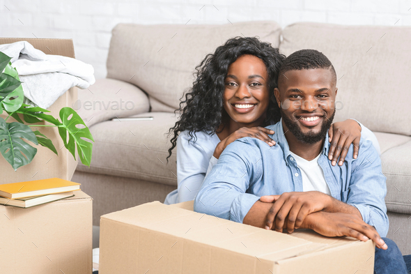 Portrait of young cheerful couple moving at new apartment - Stock Photo - Images