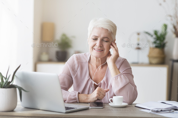 Aged business woman with earphones enjoying music - Stock Photo - Images