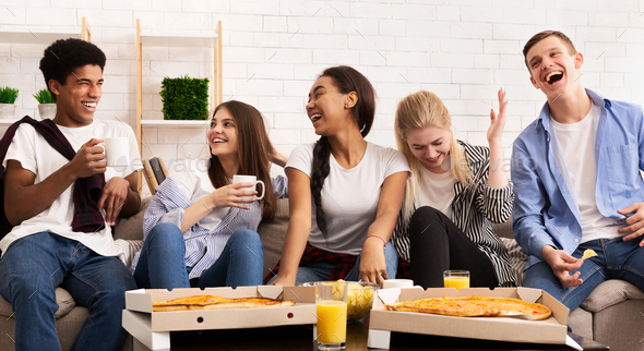 Happy teens eating pizza at home party and chatting - Stock Photo - Images