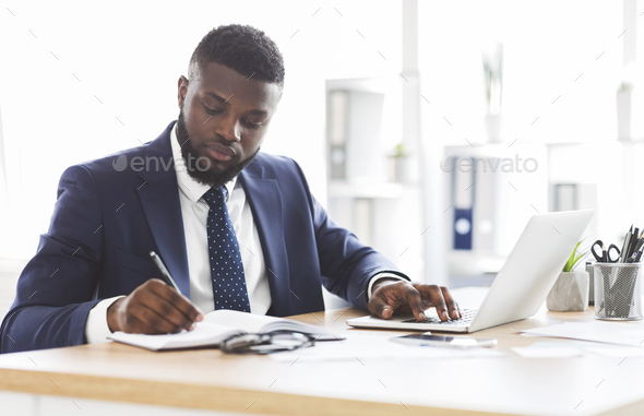 Successful black businessman working hard in office - Stock Photo - Images