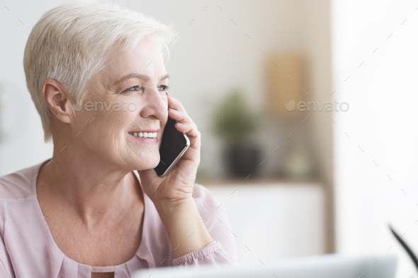 Close up of mature business woman talking by phone - Stock Photo - Images