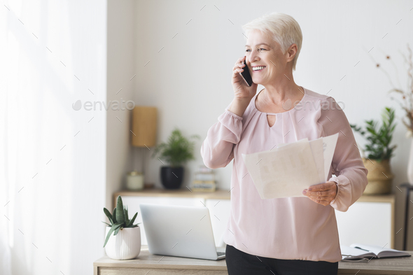 Aged business consultant talking by phone with clients - Stock Photo - Images