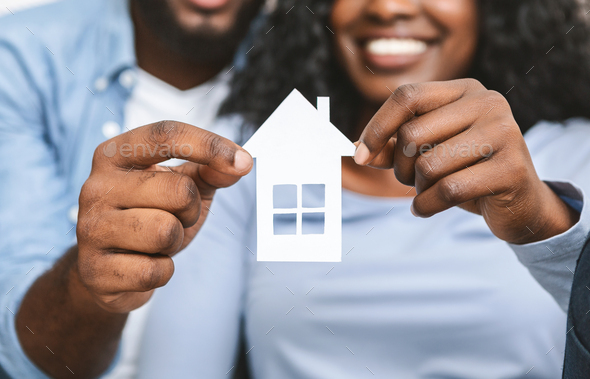 Close up of african couple holding wooden house - Stock Photo - Images