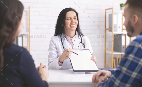 Friendly family doctor explaining prescription to patients at clinic - Stock Photo - Images