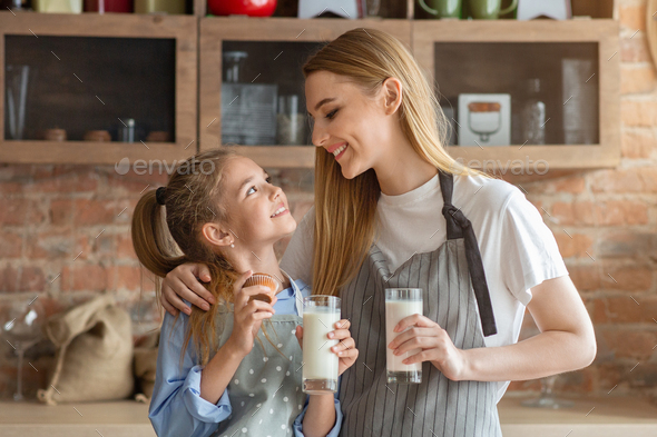Pretty mom and daughter drinking milk at kitchen - Stock Photo - Images
