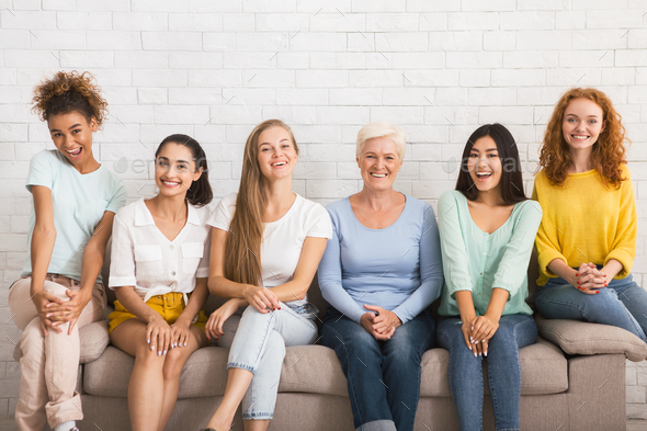 Smiling Diverse Women Sitting On Sofa Over White Brick Wall - Stock Photo - Images