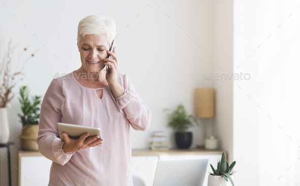 Busy senior woman consulting client on phone, using tablet - Stock Photo - Images