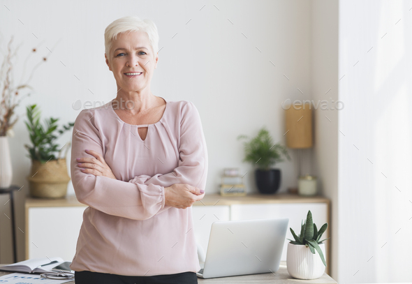 Successful senior woman posing over working place at home - Stock Photo - Images