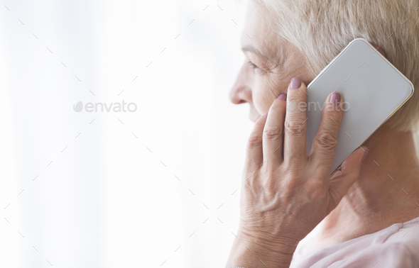 Close up of mature retired woman talking by smartphone - Stock Photo - Images
