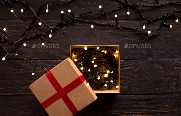 Garland with lights in gift box and on wooden background - Stock Photo - Images