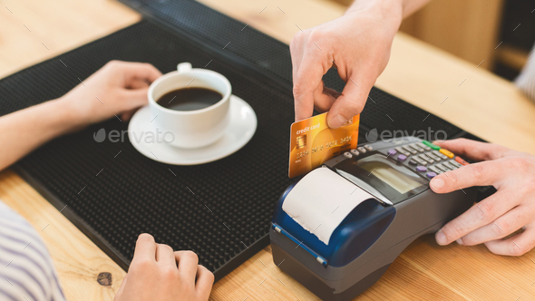 Close up of transaction with credit card in cafe for coffee - Stock Photo - Images
