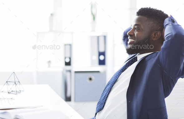 Dreamy african businessman leaning back in modern office - Stock Photo - Images