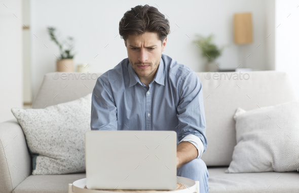 Man Working At Laptop Sitting On Couch At Home - Stock Photo - Images