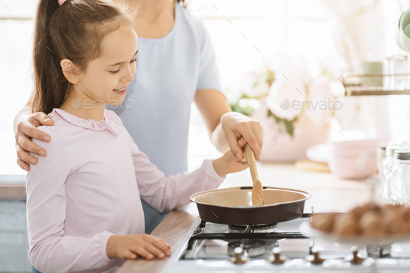 Cute little girl cooking together with mom - Stock Photo - Images