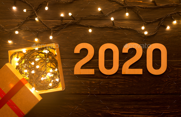 Garland with lights, gift box and 2020 concept on wood - Stock Photo - Images