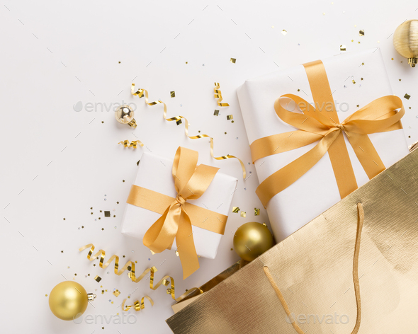 Christmas presents in gold bag with confetti on white - Stock Photo - Images
