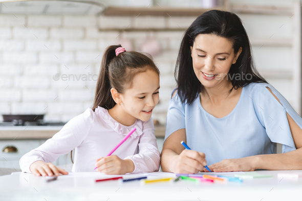 Cute little girl drawing together with her mom in kitchen - Stock Photo - Images