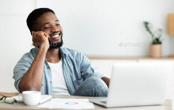 Handsome black man talking on phone while sitting at workplace - Stock Photo - Images