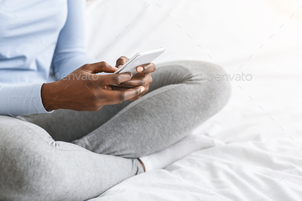 Cropped image of girl using smartphone, sitting on bed - Stock Photo - Images