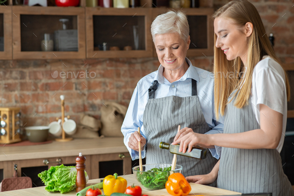 Young woman adding olive oil to healthy veggies salad - Stock Photo - Images