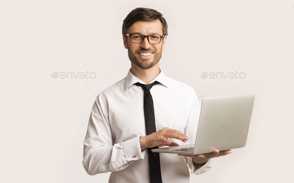Successsful Man Working On Laptop Standing Over White Background - Stock Photo - Images
