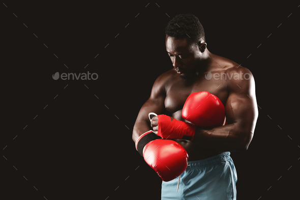 Black muscular boxer wearing red gloves before fight - Stock Photo - Images
