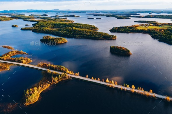 Aerial view of road bridge across blue lakes with islands and colorful autumn forest in Finland. - Stock Photo - Images