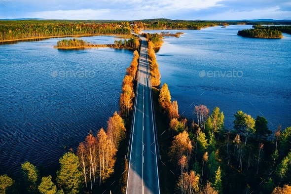Aerial view of bridge across blue lakes in colorful autumn forest in Finland. - Stock Photo - Images