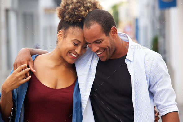 Happy couple walking together in embrace on date - Stock Photo - Images
