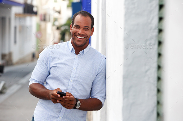 cheerful man standing outside on street with mobile phone - Stock Photo - Images