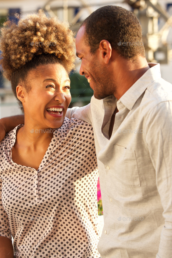 beautiful laughing couple on date standing outside - Stock Photo - Images