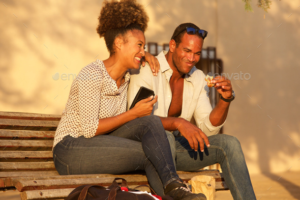 happy couple sitting on bench outside with mobile phone and snac - Stock Photo - Images