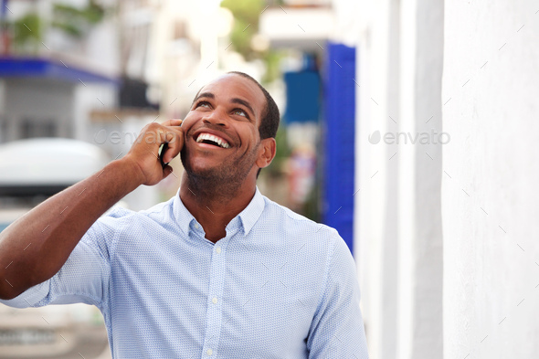 cheerful man standing outside on street talking on mobile phone - Stock Photo - Images