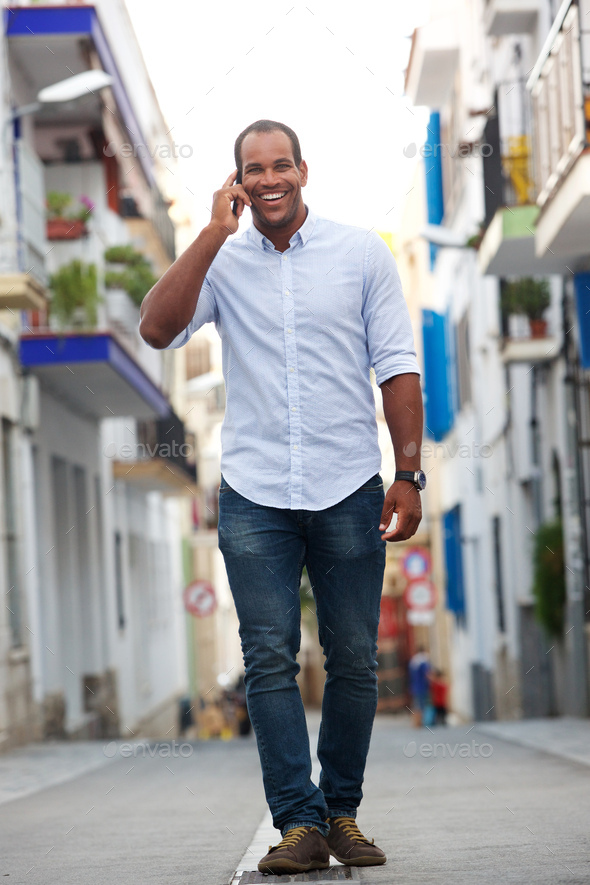 portrait of man walking on street talking on mobile phone - Stock Photo - Images