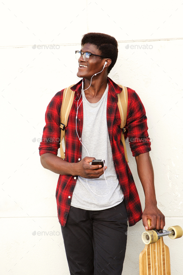 happy young black man standing with mobile phone and skateboard - Stock Photo - Images