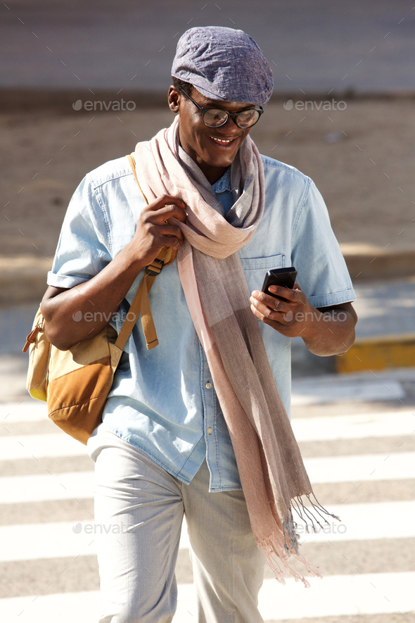 trendy young black guy walking outdoors with cell phone - Stock Photo - Images