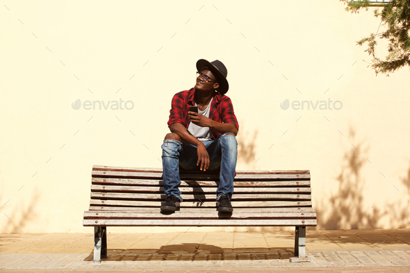cool african guy in hat sitting on bench by the street - Stock Photo - Images
