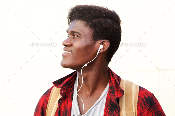 Side portrait of happy young man with earphones looking away and smiling - Stock Photo - Images