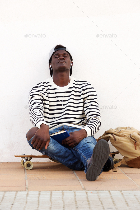 young african man sitting on skateboard by a wall with eyes closed - Stock Photo - Images